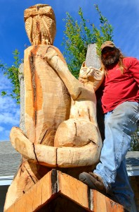 "Woodcarver Warren Hunt poses with his ""living"" sculpture on Enterprise Road."