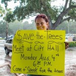 """Laura Dent holding her """"save the trees"""" sign on Bayshore Boulevard in 2014. Credit: Dave Hutchinson"""