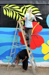Local artists Todd Ramquist and Kiaralinda paint a mural on the wall at Cox Cleaners in safety Harbor.